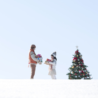 クリスマスツリーとたくさんのプレゼントを抱えた親子 20027009719| 写真素材・ストックフォト・画像・イラスト素材|アマナイメージズ