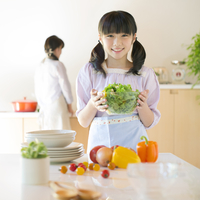 キッチンでサラダを持つ女の子