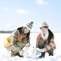 雪だるまを作る2人の女性