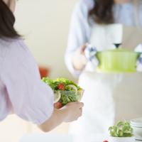 キッチンで食事の準備をする親子の手元