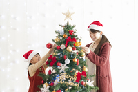 クリスマスツリーの飾り付けをする親子 20027009746| 写真素材・ストックフォト・画像・イラスト素材|アマナイメージズ
