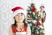 クリスマスツリーの前でケーキを持つ女の子