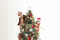 クリスマスツリーの後ろから顔を出す親子
