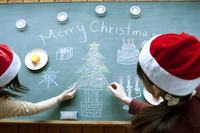 黒板にクリスマスの絵を描く親子
