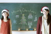 クリスマスの絵の描かれた黒板の前に立つ親子