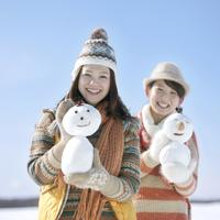 雪だるまを持ち微笑む2人の女性