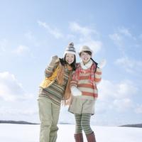 雪原で微笑む2人の女性 20027009791| 写真素材・ストックフォト・画像・イラスト素材|アマナイメージズ