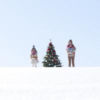 クリスマスツリーとたくさんのプレゼントを抱えた親子 20027009826| 写真素材・ストックフォト・画像・イラスト素材|アマナイメージズ