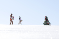 クリスマスツリーとプレゼントを運ぶ親子 20027009828| 写真素材・ストックフォト・画像・イラスト素材|アマナイメージズ