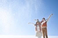 雪原で雪を舞い上げる親子 20027009831| 写真素材・ストックフォト・画像・イラスト素材|アマナイメージズ