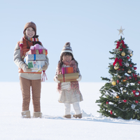 たくさんのプレゼントを抱える親子とクリスマスツリー