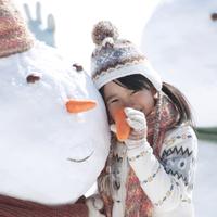 雪だるまの側で人参を持つ女の子