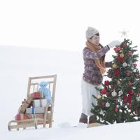 クリスマスツリーの飾り付けをする女性 20027009854| 写真素材・ストックフォト・画像・イラスト素材|アマナイメージズ