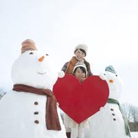 雪だるまの側でハートを持つ親子
