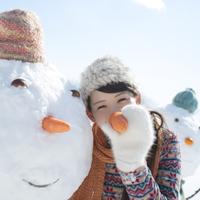 人参を持ち雪だるまの真似をする女性