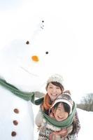 雪だるまと同じマフラーに包まる親子