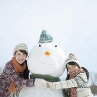雪だるまに抱きつく親子