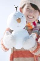 雪だるまを持ち微笑む女性