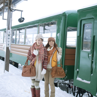 列車の前で微笑む2人の女性