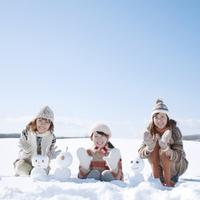 雪原で雪だるまを作り微笑む3人の女性