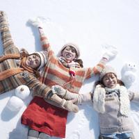雪原に寝転ぶ3人の女性と雪だるま