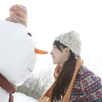 雪だるまに顔を近づけ微笑む女性