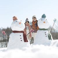 雪だるまの側で微笑む親子