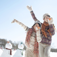 人参を持ち雪だるまの真似をする親子
