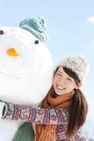雪だるまに抱きつく女性