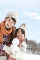 雪だるまを持ち微笑む親子