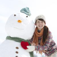 雪だるまの側でハートを持つ女性