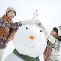 雪だるまの上に小さな雪だるまを乗せる親子