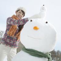 雪だるまの上に小さな雪だるまを乗せる女性