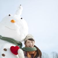 雪だるまと同じマフラーに包まる女性