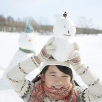 頭の上に雪だるまを持ち微笑む女の子