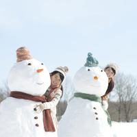 雪だるまの後ろから顔を出す親子
