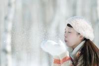 雪に息を吹きかける女性