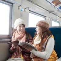 列車の中で雑誌を見る2人の女性