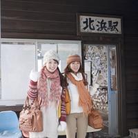 駅の前に立つ2人の女性