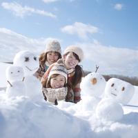 雪原に寝転び微笑む3人の女性と雪だるま