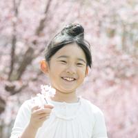桜を持ち微笑む女の子