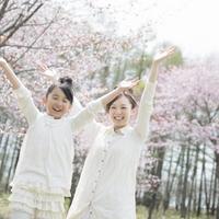 桜の前で両手を広げる親子