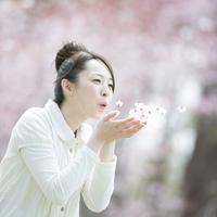 桜の花びらを吹く女性 20027010054| 写真素材・ストックフォト・画像・イラスト素材|アマナイメージズ