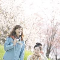 カメラを持ち微笑む2人の女性 20027010065| 写真素材・ストックフォト・画像・イラスト素材|アマナイメージズ