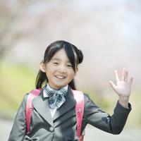 桜の前で手を振る女の子 20027010071| 写真素材・ストックフォト・画像・イラスト素材|アマナイメージズ