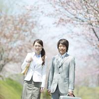 桜の前で微笑むビジネスウーマンとビジネスマン