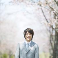 桜の前で微笑むビジネスマン