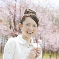 桜を持ち微笑む女性
