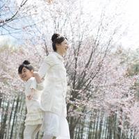 桜の前で背中合わせに立つ親子