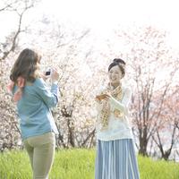 桜の前で写真を撮る2人の女性